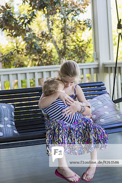 Caucasian girl holding brother on porch swing