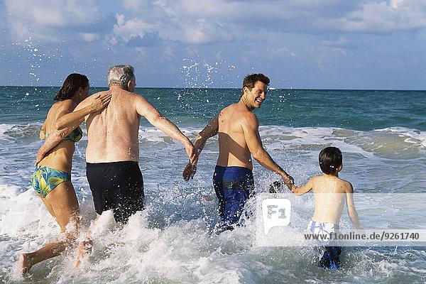 Family walking in waves on beach