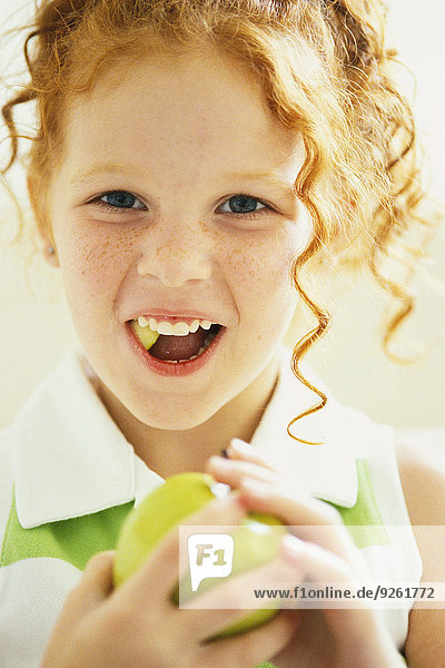 Smiling girl eating apple