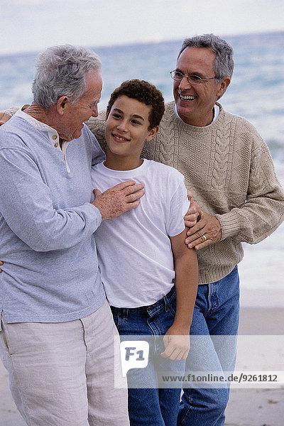 Three generations of Caucasian men walking on beach