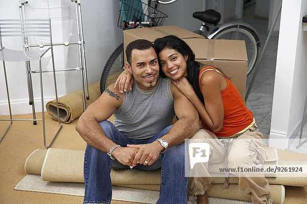 Hispanic couple smiling in new home