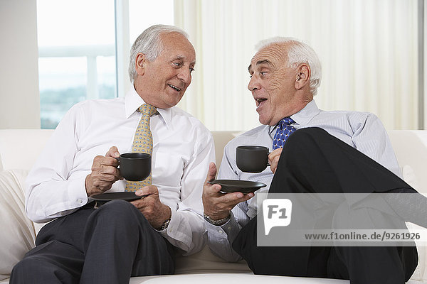 Senior businessmen having coffee on sofa