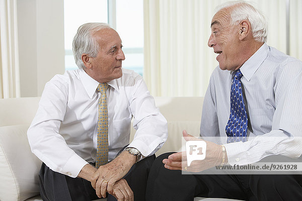 Senior businessmen talking on sofa