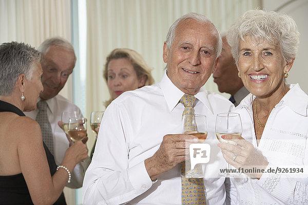Senior couple having wine at dinner party