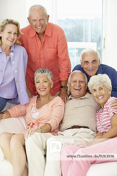 Senior friends smiling together in living room