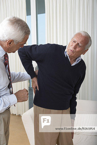 Senior man seeing doctor about back pain