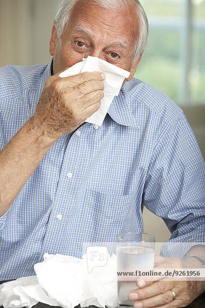 Senior man wiping his nose