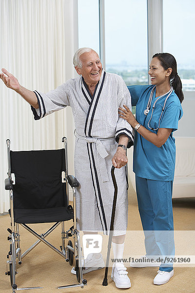 Nurse helping Senior patient use cane