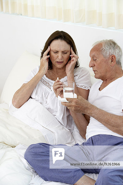 Senior man giving wife painkillers in bed