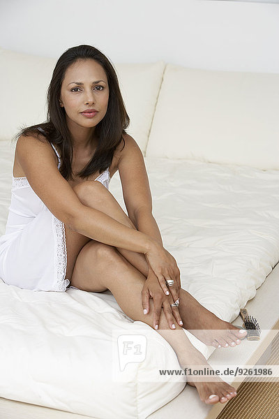 Indian woman sitting on bed