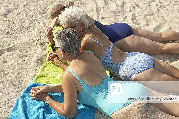 Senior women laying on beach