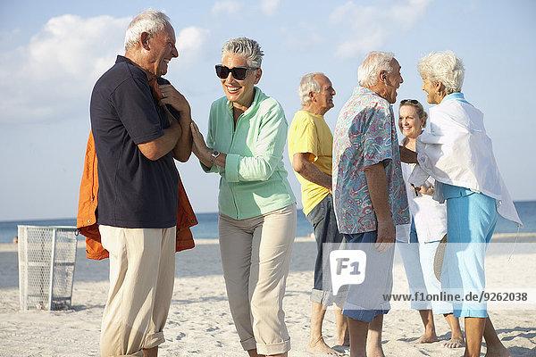 Senior friends talking on beach