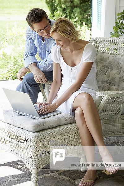 Couple using laptop together on patio