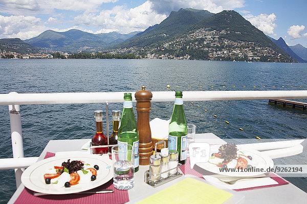 Plates of food at restaurant overlooking rural lake  Lugano  Ticino  Switzerland