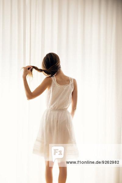 Junge Frau spielt mit ihrem Haar vor einem weißen Vorhang  Rückansicht