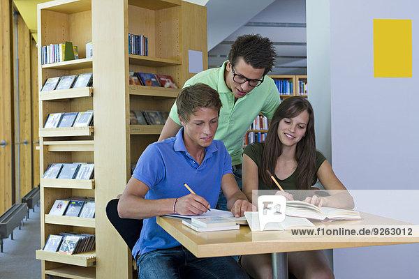 Deutschland  Baden-Württemberg  drei Studenten lernen in einer Bibliothek