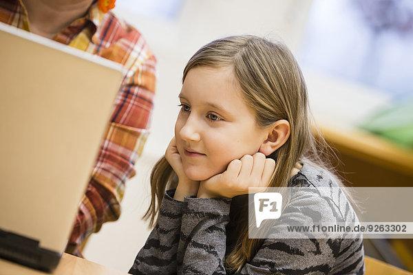 Porträt einer Schülerin beim Blick auf den Laptop