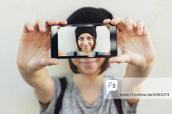 Young female skate boarder hiding behind smartphone with her selfie