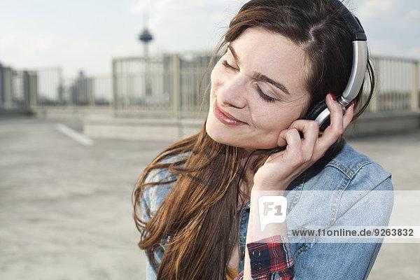 Deutschland  Nordrhein-Westfalen  Köln  Portrait einer lächelnden jungen Frau beim Musikhören mit Kopfhörern