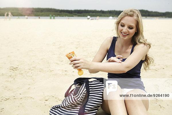 Lächelnde junge Frau am Strand sitzend mit Sonnencreme