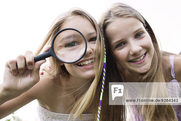 Portrait of two smiling girls with magnifying glass