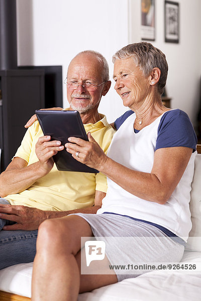 Seniorenpaar auf der Couch sitzend mit digitalem Tablett