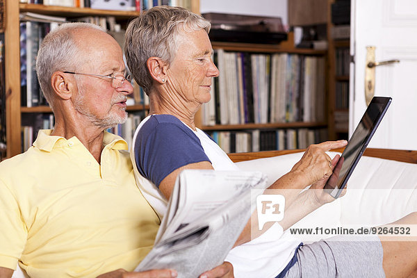 Senior couple sitting on couch with newspaper using digital tablet