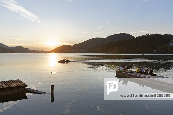 Austria  Salzburg State  Fuschlsee Lake  Fuschl am See  Wooden boardwalk and people at sunset
