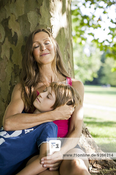 Germany  Berlin  Mother in park with sleeping son