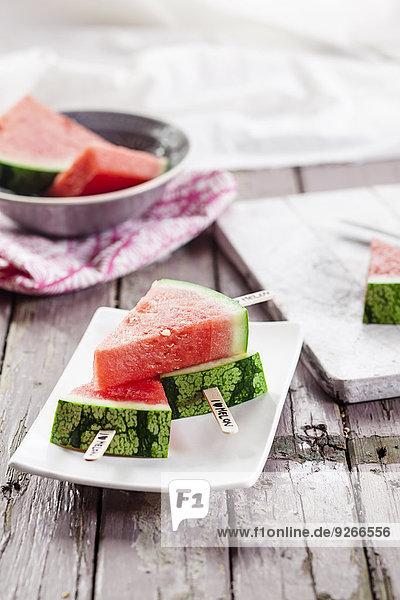 Schale und Teller aus Melonenpopsicles auf Stoff und Holz