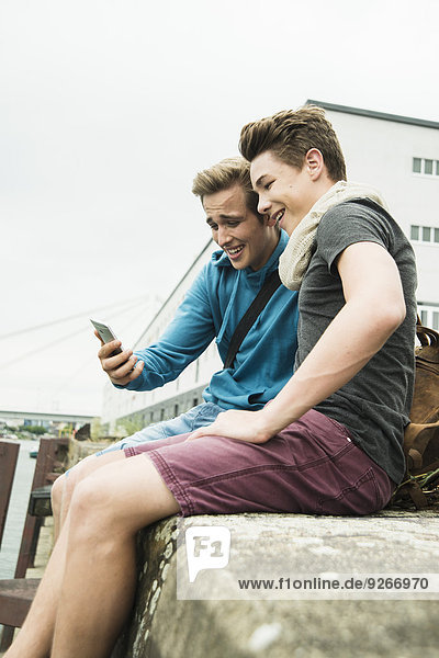 Two happy friends with cell phone outdoors