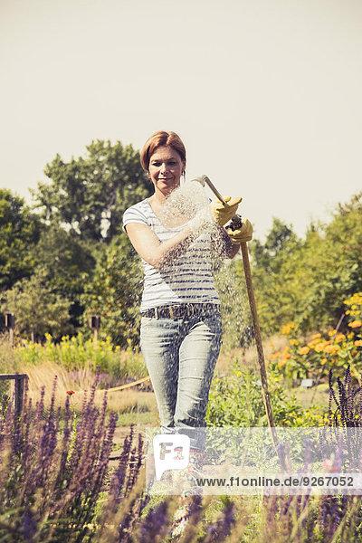 Reife Frau beim Blumen gießen