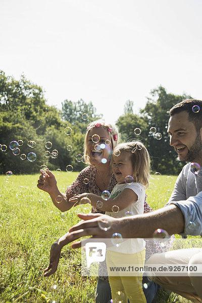 Eltern und kleine Tochter machen Seifenblasen auf einer Wiese