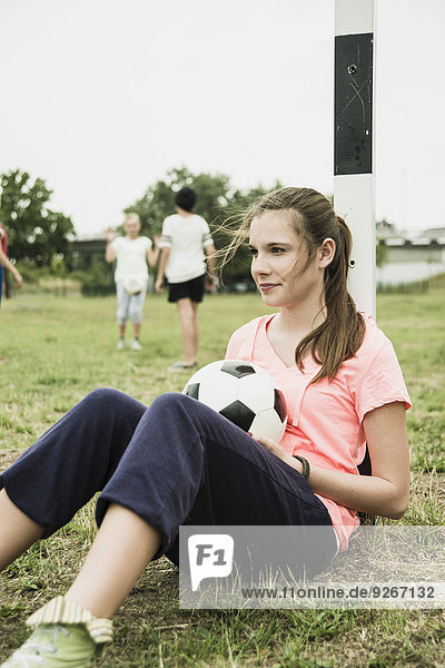 Portrait of smiling teenage girl with soccer ball leaning at goalpost