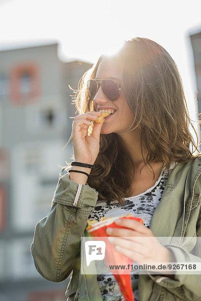 Porträt eines Mädchens mit Sonnenbrille  das Pommes frites isst.