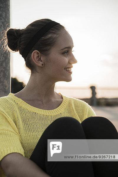 Profil eines lächelnden Teenagers  der in der Abenddämmerung auf einer Parkebene sitzt.