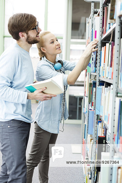 Two students in a university library taking book from shelf