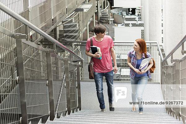 Zwei Studenten in einer Universitätsbibliothek gehen nach oben.