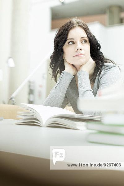 Abgelenkter Student in einer Universitätsbibliothek