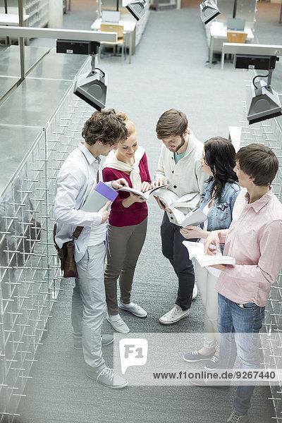 Studentengruppe  die in einer Universitätsbibliothek lernt