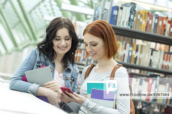 Zwei Studenten in einer Universitätsbibliothek mit Handy