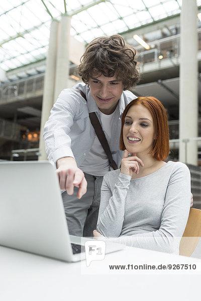 Zwei Studenten mit Laptop in einer Universitätsbibliothek