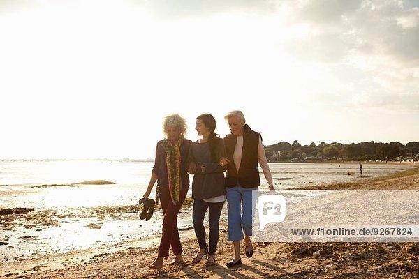 Weibliche Familienmitglieder  die am Strand spazieren gehen