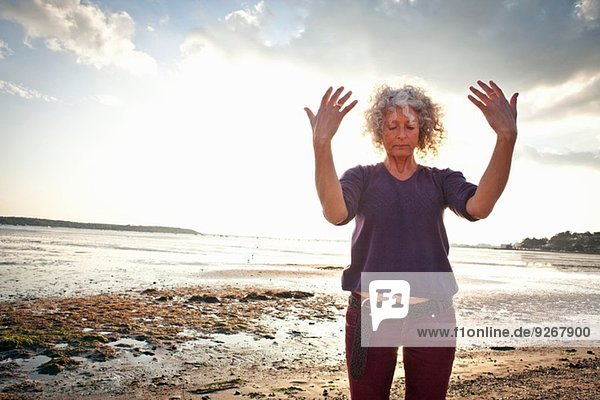 Reife Frau beim Training am Strand