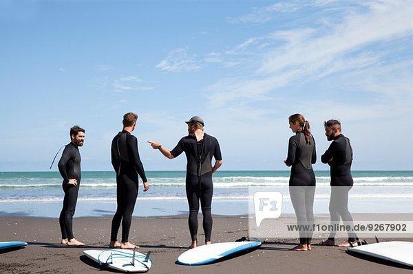 Gruppe von männlichen und weiblichen Surferfreunden beim Plaudern am Strand