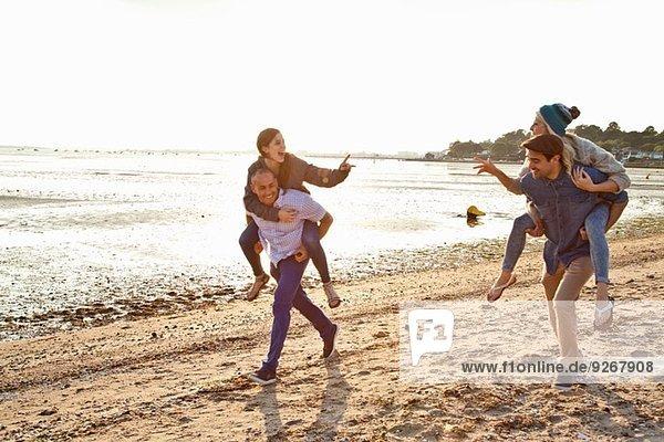 Männer beim Huckepackfahren für Frauen am Strand