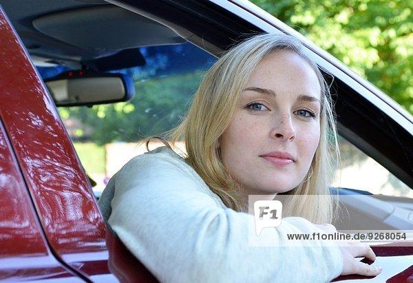 Porträt einer jungen Frau  die durch das Autofenster schaut.
