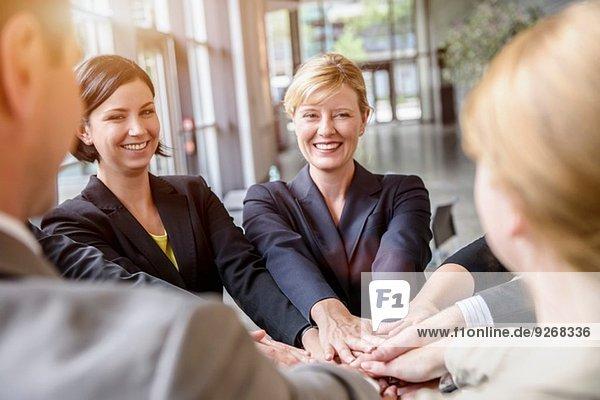 Gruppe von Geschäftsfrauen und Männern im Kreis mit gemeinsamen Händen