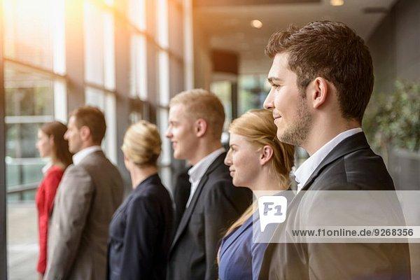 Gruppe lächelnder Geschäftsfrauen und Männer  die in einer Reihe stehen