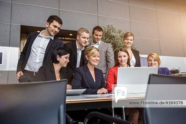 Businesswoman and office team looking at laptop
